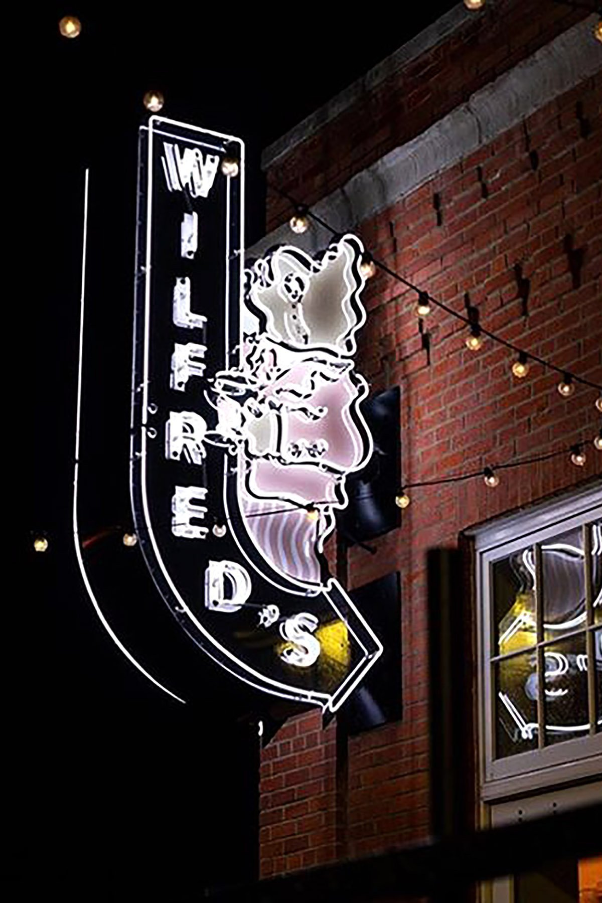 Night shot of projecting neon sign for Wilfred's